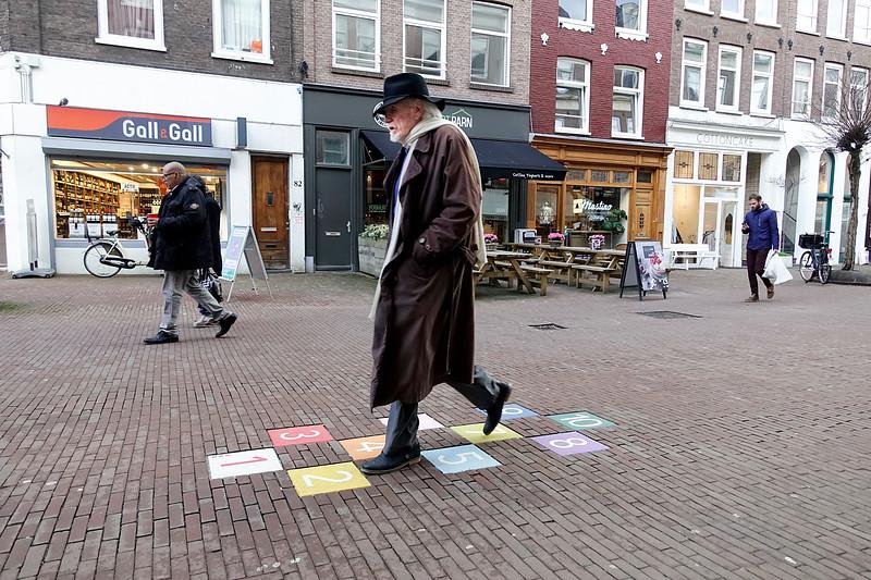 Nederland, Amsterdam, eerste van der Helststraat in de Pijp, een bohemien loopt waar hij moet hinkelen, 2 maart 2017, foto: Katrien Mulder