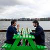 Nederland, Amsterdam, Amsterdam Noord, langs het IJ, met uitzicht op het Javaeiland, oken; drinken; bier; gesprek; vrienden; discussietwee mannen drinken bier en roken sigaretten, 26 april 2017, foto: Katrien Mulder