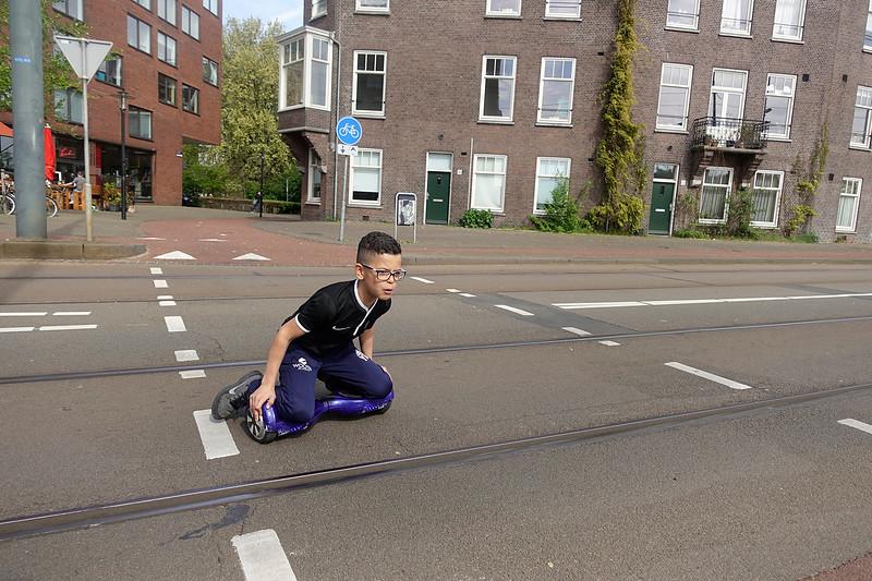 Nederland, Amsterdam, Oostelijk Havengebied, jongen racet op hoverboard over straat, 30 april 2017, foto: Katrien Mulder