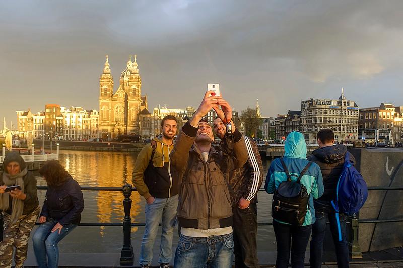Nederland, Amsterdam, Avondzon tijdens regenbui op het Stationsplein; 12 mei 2017, foto: Katrien Mulder