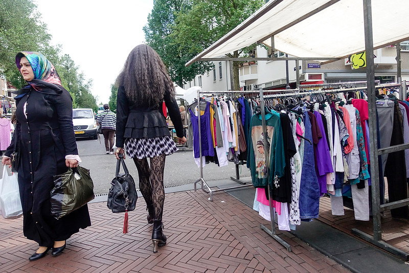 Nederland, Amsterdam, Dappermarkt, een lange vrouw met opvallende netkousen passeert Turkse vrouw met hoofddoek, A tall woman with striking fishnet stockings passes Turkish woman with headscarf 26 juni 2017, foto: Katrien Mulder