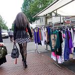 Nederland, Amsterdam, Dappermarkt, een lange vrouw met opvallende netkousen passeert Turkse vrouw met hoofddoek, A tall woman with striking fishnet stockings passes Turkish woman with headsc ...