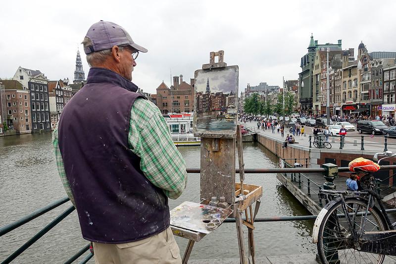 Nederland, Amsterdam, kunstschilder hoek Damrak PrinsHendrikkade, 28 juni 2017, foto: Katrien mulder