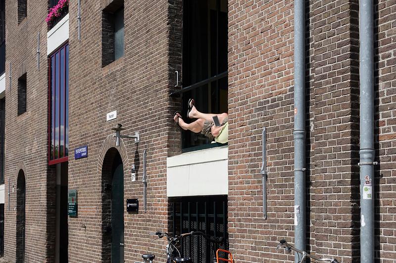 Nederland, Amsterdam, met e-reader voor het open raam in de zon, 9 juli 2017. foto: Katrien Mulder
