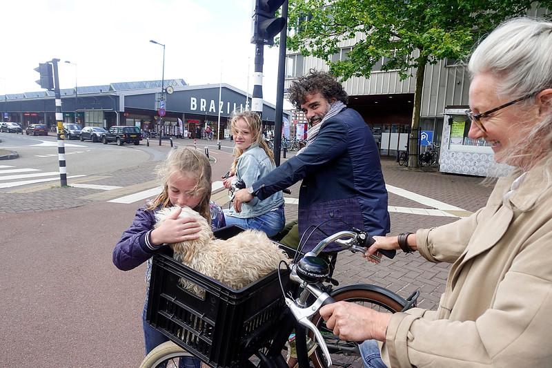 Nederland, Amsterdam, meisje kust hondje dat in een fietsbak van zijn bazin meerijdt, 14 juli 2017, foto: Katrien Mulder