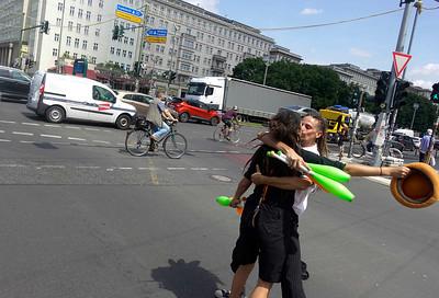 """Duitsland, Berlijn, 20 juli 2017, Alba en Dani uit Alicante, jongleren met kegels. Dat is hun werk. Jongleren  op drukke kruispunten voor auto's zolang het stoplicht op rood staat, daarna vliegensvlug met de pet rond, voordat de auto's op stoom zijn en wegracen.Ze doen het overal in Europa. In Italie, daar verdienen ze het meest. In Frankrijk hadden ze laatst in een uur dertig euro binnen een uur. In Berlijn hebben ze geen ervaring, ze staan hier nu  een paar uur, en het gaat redelijk. Ze hebben zoveel spaanse vrienden in Berlijn, dat ze een week geen tijd hadden om te jongleren. Maar vandaag zei Dani :""""komop, aan het werk"""".foto: Katrien Mulde"""