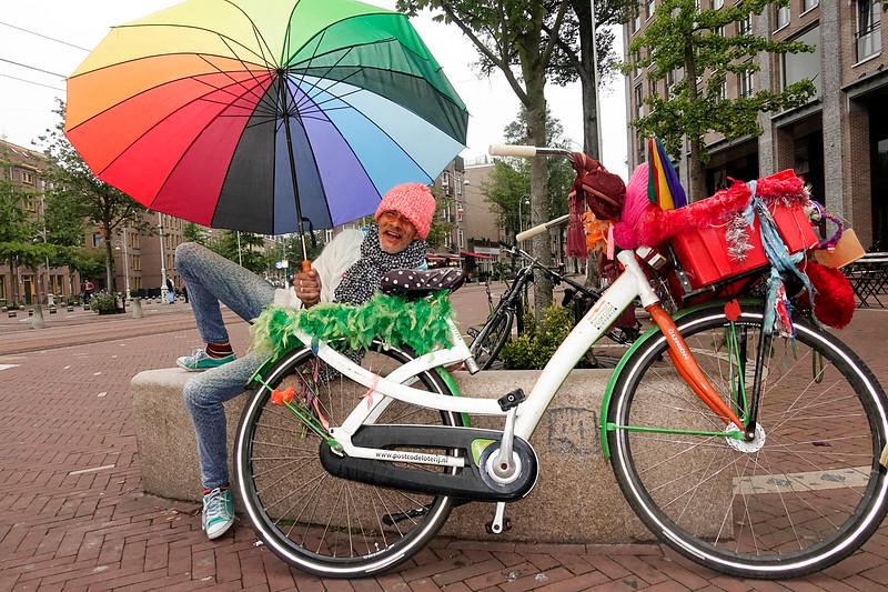 Nederland, Amsterdam, 17 augusttus 2017,  Wahid, Marokkaanse man met regenboog paraplu en versierde fiets, op zijn vaste plek op een muurtje op het Javaplein, foto: Katrien Mulder