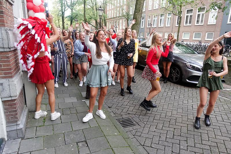 Nederland, Amsterdam, 19 augustus 2017, Na de ontgroeninsperiode van het Amsterdmse Sudentencorps moeten  de nieuwe leden kiezen voor een dispuut. Ook het dispuut moet  aangeven welke aspirant leden ze graag willen hebben. Het is een enorm getouwtrek. De nieuwelingen moeten worden overgehaald voor het dispuut te kiezen  dat ze zojuist bezocht hebben en dat hen  vanuit de verte nazingt, een paar ouderejaars  lopen nog een stukje mee om te voorkomen dat ze voor een ander dispuut zullen kiezen.foto: Katrien Mulder