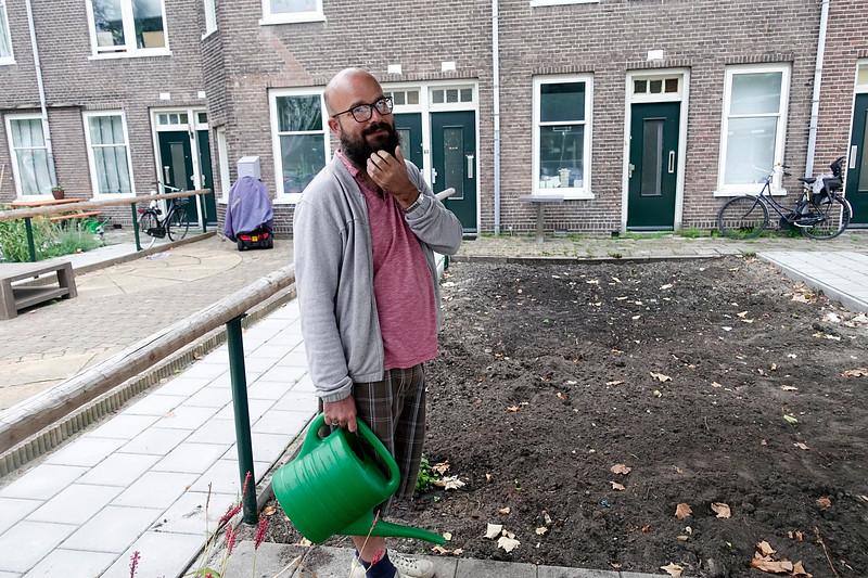 Nederland, Amsterdam, Meeuwenlaan, 6 september 2017, Geen groen te bekennen. De vorige bewoner liet zijn honden  hier uit.  De nieuwe, Michael uit Londen,  heeft plannen. Hier kruiden, daar groente,  fruit en bloemen. Hij  geeft zijn toekomstdroom vast water,   ofschoon de  buien vabdaag niet van de lucht zijn. foto: Katrien Mulder