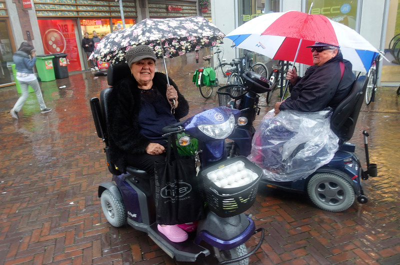 Nederland, Amsterdam, 8 september 2017, Twee ouderen met scootmobiel in de regen in winkelcentrum oostpoort; foto: Katrien Mulder