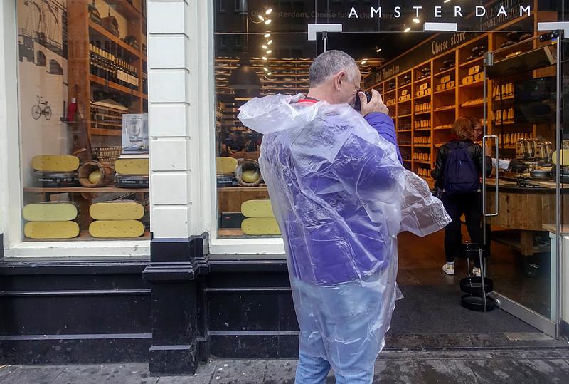 Nederland, Amsterdam, 11 september 2017, toerist in regenponcho fotografeert kaaswinkel;   foto: Katrien Mulder