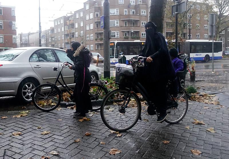 Nederland, Amsterdam, 18 november 2017, nikab dragende vrouw op fiets met kinderen, Insulindewegfoto: Katrien Mulder