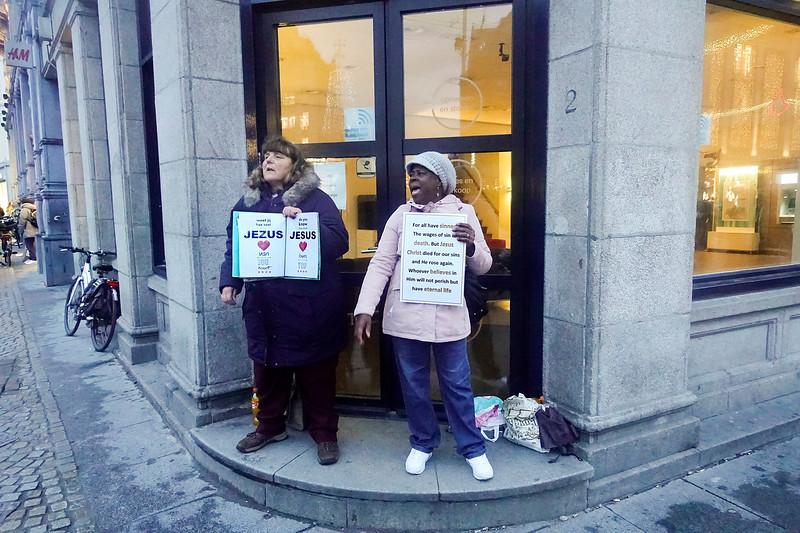 Nederland, Amsterdam, hoek Damrak en Dam,  Twee vrouwen roepen voorbijgangers op zich tot het christelijke geloof te bekeren, 8 november 2017, foto: Katrien Mulder