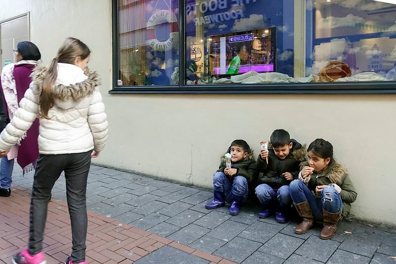 Nederland, Amsterdam, 24 november 2017, black friday, drie kinderen eten een ijsje op de stoep van de Nieuwendijk terwijl hun oma en hun moeder zzn het shoppen zijn bij de Primark, foto: Katrien Mulder