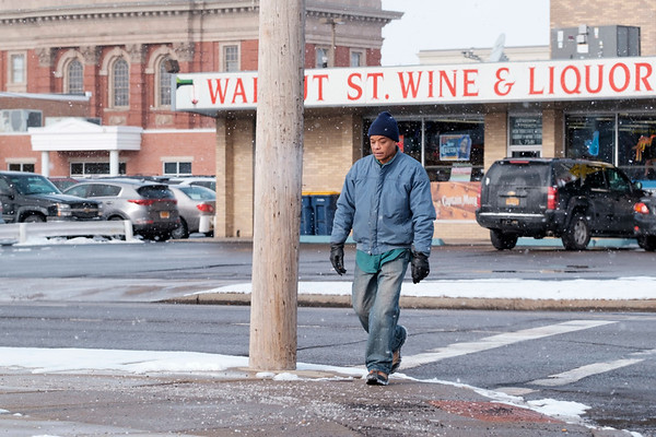 Joed Viera/Staff Photographer- Lockport, NY-Clifford Davis crosses Walnut Street at Washburn Street on his way to the Niagara Community Action Program, Inc's Pantry.