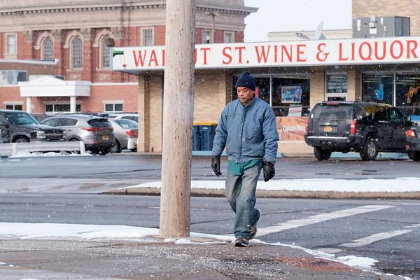 Joed Viera/Staff Photographer- Lockport, NY-Clifford Davis crosses Walnut Street at Washburn Street on his way to the Niagara Community Action Program, Inc's Pantry.