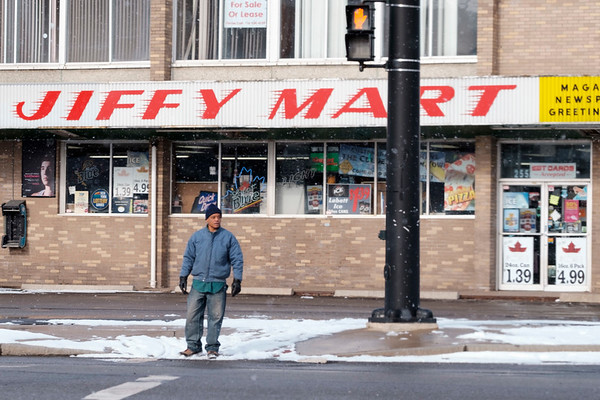 Joed Viera/Staff Photographer- Lockport, NY-Clifford Davis crosses Walnut Street at Washburn Street on his way to the Niagara Community Action Program, Inc.