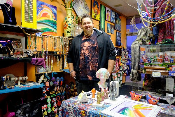 Joed Viera/Staff Photgrapher-Earth House's featured artist Garrett Dykstra stands surrounded by his sculptures and paintings inside the shop on Wendesday.