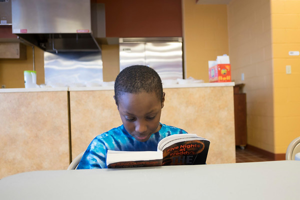 "Joed Viera/Staff Photographer-Tyson Triplette, 8, reads ""Five Nights at Freddy's"" inside the Williamsville YMCA's kitchen."