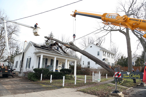 Stephen Wallace/Contributer-Lockport, NY-Crews work on removing a fallen tree laying on the collapsed roof of 220 Erie Street.