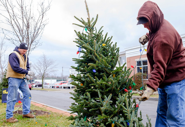 Joed Viera/Staff Photgrapher-City workers Mark Sobieraski and Roy Gugliuzza remove holiday decorations from the trees on Main Street's medians on January, 4, 2016 in Lockport, N.Y. For residents wondering what to do with their Christmas trees: In the Town trees are considered one of residents six bags of refuse. In the City trees are considered separate from normal garbage and are picked up by the city chipper which goes out year round and loosely follows the garbage route. It is recommended to not wrap the trees and to place the trunks out towards the curb.