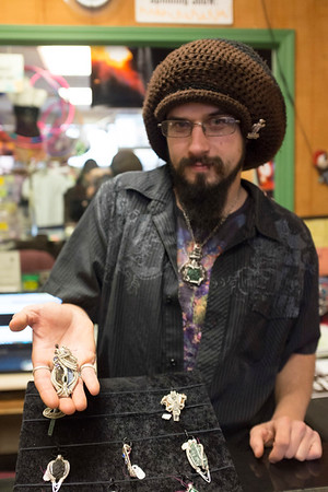 Joed Viera/Staff Photographer-Kyle Melancon holds a piece of jewlery  he made at his shop Earth House.