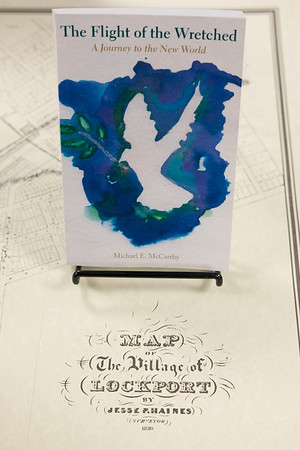 Joed Viera/Staff Photographer-Lockport, NY-A copy of Michael E McCarthy's Flight of the Wretched sits on a map of the village of Lockport inside the Erie Canal Discovery Center.