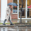 Joed Viera/Staff Photographer-Lockport, NY-A man carries an umbrella while walking down Main Street towards his car on an unusually rainy January day.