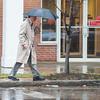 Joed Viera/Staff Photographer-Lockport, NY-A man carries an umbrella while walking down Main Street towards his car on an unusually rainy January day.