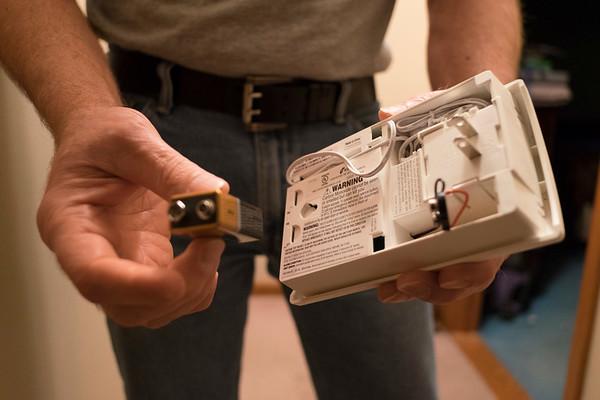 Joed Viera/Staff Photographer-John Pinzel checks the battery in his carbon monoxide alarm.