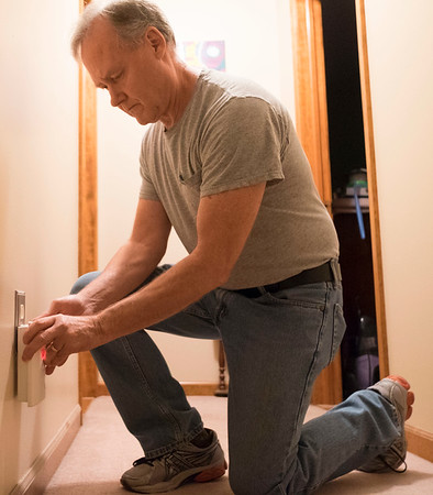 Joed Viera/Staff Photographer-John Pinzel plugs in his carbon monoxide alarm.