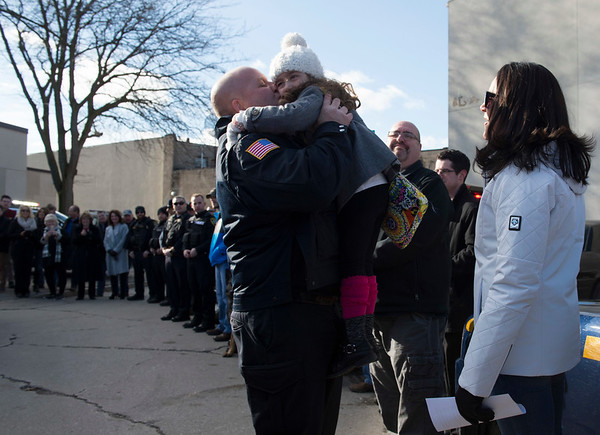 Joed Viera/Staff Photographer-Lockport, NY- Tara Wasik watches as Lockport Police patrolman Mike Wasik hugs his daughter Natalie, 5, towards the end of his last walk.