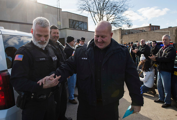 Joed Viera/Staff Photographer-Lockport, NY- Lockport Police patrolman Mike Wasik shakes hands with Officer Mike Stover  during his last walk. The pair started on the force around the same time.