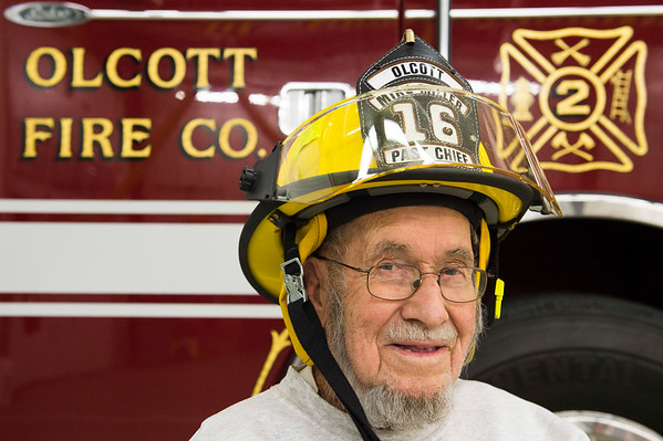 Joed Viera/Staff Photographer-Olcott ,NY- Clifford Miller Sr wears his grandson's hat in front of Olcott Volunteer Firefighter Engine No 2. Miller, 93, has been a member for 74 years. Four generations of the Miller family have been involved with the Company.