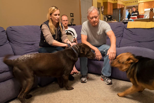 Joed Viera/Staff Photographer-Laurie, Joe and John Pinzel play with their dogs in their family room.
