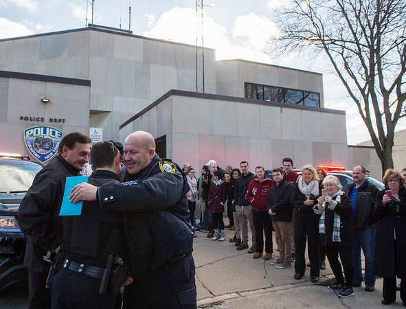 Joed Viera/Staff Photographer-Lockport, NY- Retiring Lockport Police patrolman Mike Wasik hugs Adam Szwartz during his last walk. Szwartz is one of police department's newest officers.