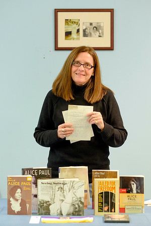 Joed Viera/Staff Photographer-Lockport ,NY- Mary Brennan-Taylor stands behind books about Alice Paul and the suffrage movement while holding one of the letters Paul wrote to her after the women met in 1976.