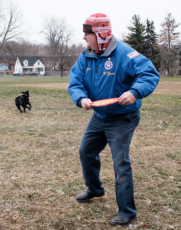 Joed Viera/Staff Photographer-John Briggs plays catch with Maverick at Dolan Park. Briggs takes out the black labrador everyday weather permitting.
