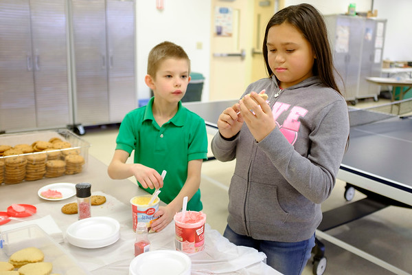 JOED VIERA/STAFF PHOTOGRAPHER-Lockport, NY-Fredrick Saraf, 9, and Faithe Cruz, 10,decorate cookies for themselves as a reward after making Valentine's Day gift bags for residents of Presbyterian Home after school at the Salvation Army.