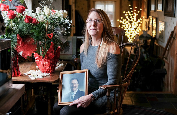 Joed Viera/Staff Photographer- Lockport, NY- Cynthia Hahn-Davis sits holding a portrait of her brother Steve Hahn at her flower shop.