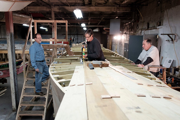 JOED VIERA/STAFF PHOTOGRAPHER-Buffalo, NY-Tom Glynn, Kevin Minderler and Skip Hauenstein work on the Erie Traveler during the Thursday night shift at the Buffalo Maritime Center. The volunteers adhered frames to the Durham Style boat.