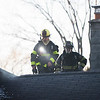Joed Viera/Staff Photographer- Lockport, NY- City firefighters work on the roof at the scene of a fire on 67 Olcott Street.