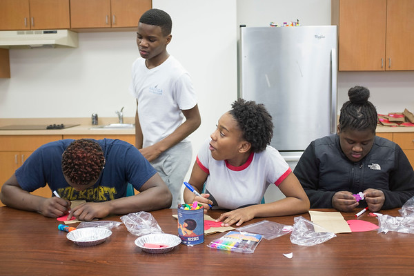 JOED VIERA/STAFF PHOTOGRAPHER-Lockport, NY-Antwaan Hill, 15, Collin Thompson, 13, Jordan Chandler, 13, and Carmella Hill, 12, make Valentine's Day gift bags for residents of Presbyterian Home after school at the Salvation Army.