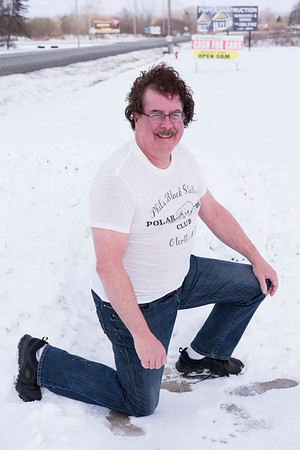JOED VIERA/STAFF PHOTOGRAPHER-Lockport, NY-Tim Durfy takes a knee in the snow while wearing a decades old polar bear club t-shirt  outside of his shop on Rochester Road.