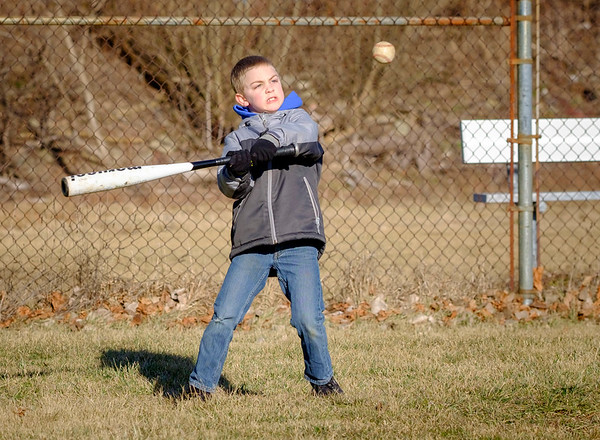 JOED VIERA/STAFF PHOTOGRAPHER-Lockport, NY-Connor Platter, 8, keeps his eye on the prize while practicing his swing with his cousins at Dolan Park.
