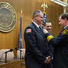Joed Viera/Staff Photographer- Lockport, NY- Newly promoted Lockport Fire Department Captain James Scapelliti looks on as chief Pat Brady promotes firefighter Jon Fredrickson to Liutenant during a ceremony in the City Council Chamber.