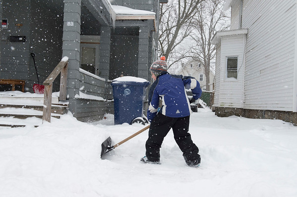JOED VIERA/STAFF PHOTOGRAPHER-Lockport, NY-Tyrec McGill, 9, takes advantage of a snow day to make $5 shoveling a driveway on South Street.