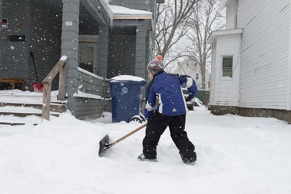 JOED VIERA/STAFF PHOTOGRAPHER-Lockport, NY-Tyrec McGill, 9, takes advantage of a snow day to make $5 shoveling a driveway on South Street.