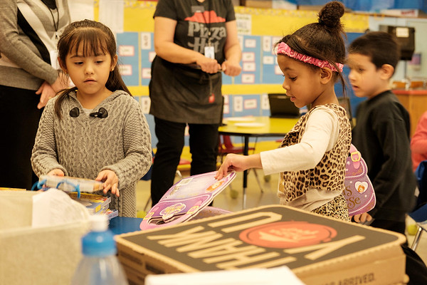 Joed Viera/Staff Photographer Lockport, NY-Regina montes Vargas, 6, and Shaylianis Gonzales Martinez, 5, pick out books to take home in Margot Collins' Kindergarten class at George Southard Elementary School.  Students at the school received 1,000 books and a pizza party from Pizza Hut's The Literacy Project.
