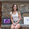 JOED VIERA/STAFF PHOTOGRAPHER-Wilson, NY-Wilson High School senior Katie Johnston, 18, sits by her self portrait and Wilson Bicentenial logo. Johnston entered her works into Wilson High School's 15th Annual Art Show.